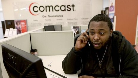 A customer service representative talks on a headset at a Comcast call center in Florida.