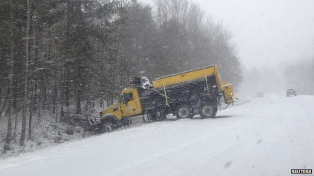 A snowplough finds itself in the ditch after sliding off a snow-covered North Carolina Highway 54 near Saxapahaw, North Carolina February 12, 2014.
