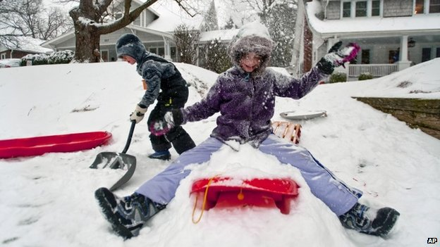Nine-year-old Katie Swayne, right, throws snow into the air as her brother Bradley, 6, shovels a path in front of their house while the snow continues to fall in Winston-Salem,  North Carolina 12 February 2014