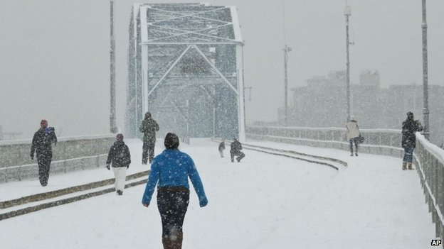 Pedestrians walk across the Walnut Street Bridge as snow accumulates on  in Chattanooga, Tennessee 12 February 2014
