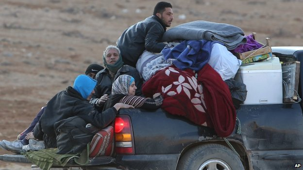 Syrians flee the town of Yabroud on the back of a truck. Photo: 12 February 2014