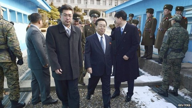 Head of the North Korean high-level delegation Won Tong Yon (C) crosses the concrete border which separates the two Koreas at the truce village of Panmunjom in the demilitarised zone on 12 February 2014