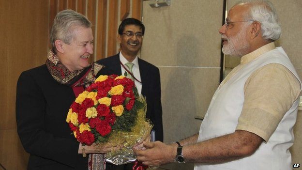 US Ambassador to India, Nancy Powell, left, receives flowers presented to her by India's opposition Bharatiya Janata Party's prime ministerial candidate Narendra Modi