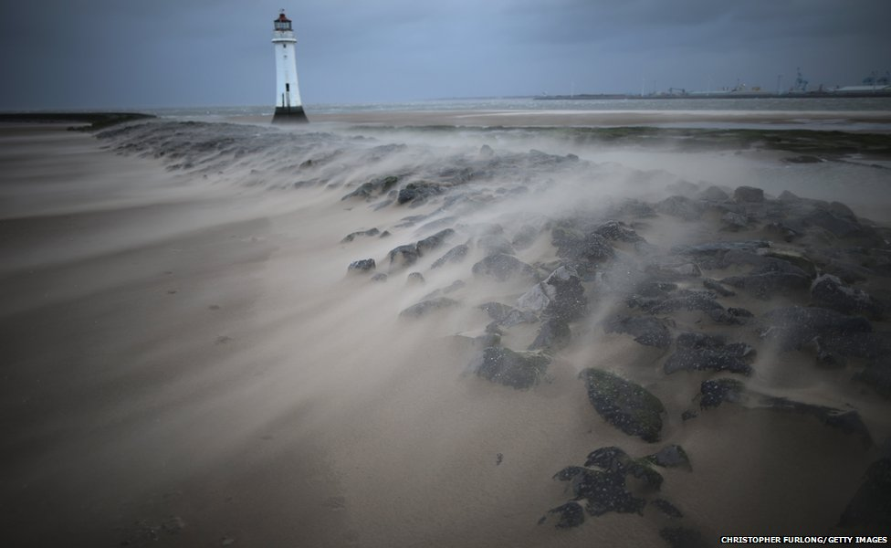A miniature sandstorm blows across the breakwater next to the Perch Rock lighthouse on in New Brighton, United Kingdom