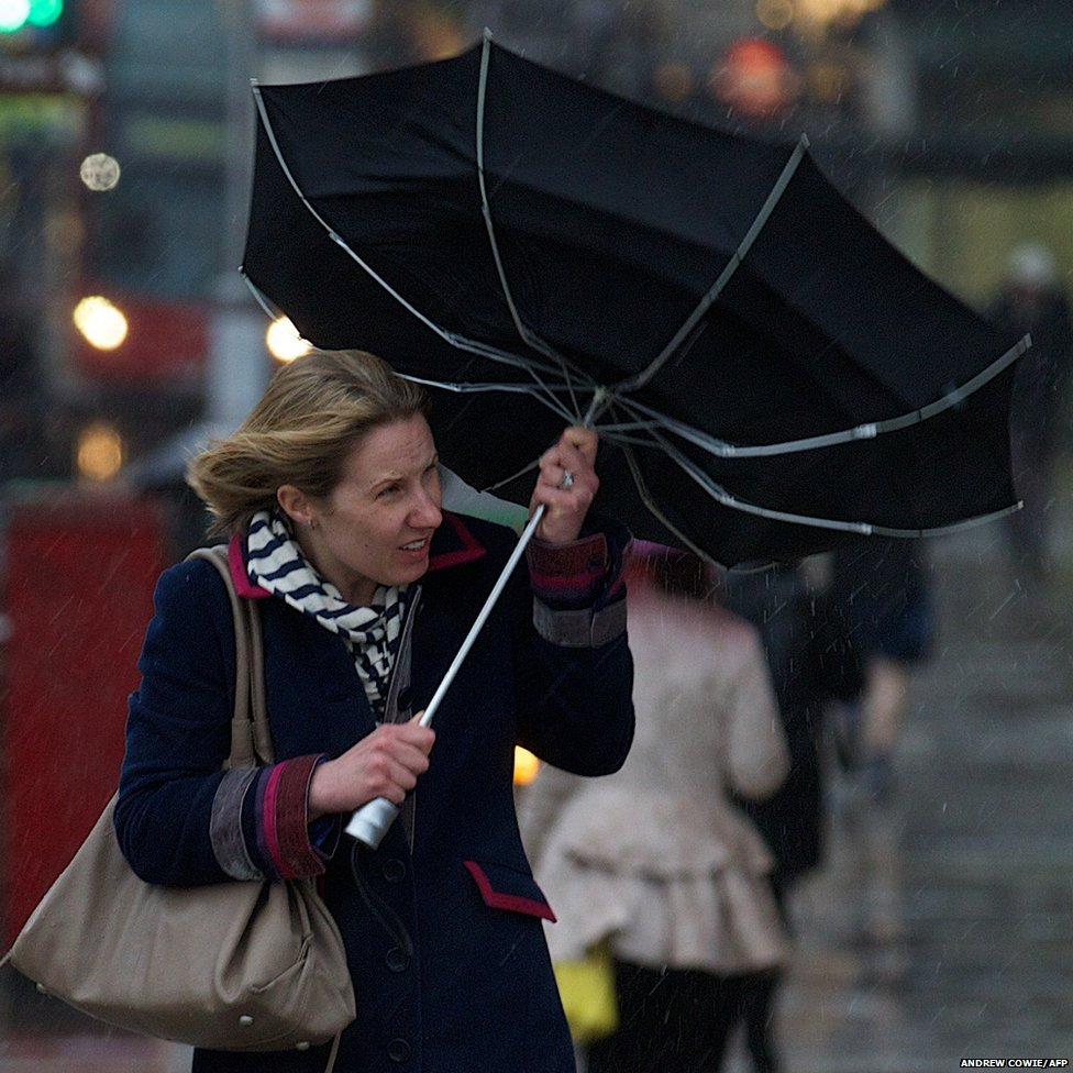 A woman battles the high winds with her umbrella as she walks across a bridge in central London