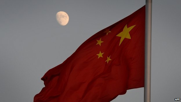 The Chinese flag is seen in front of a view of the moon at Tiananmen Square in Beijing on 13 December 2013