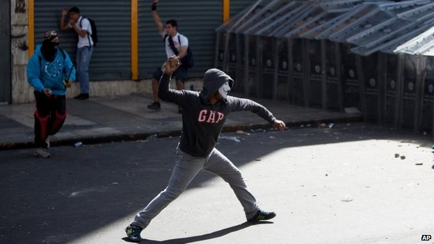 Demonstrators throw rocks at riot police during clashes between opposition protesters with security forces and pro-government supporters during a protest against the government in Caracas on 12 February, 2014
