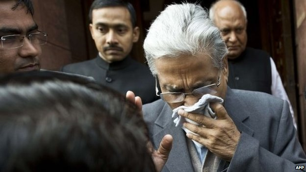 "An unidentified member of India""s Parliament, holding a handkerchief to his face after being affected by pepper spray, leaves Parliament after protests inside the building in New Delhi on February 13, 2014."