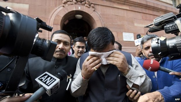 "An unidentified member of India""s Parliament, holding a handkerchief to his face after being affected by pepper spray, leaves Parliament after protests inside the building in New Delhi on February 13, 2014"