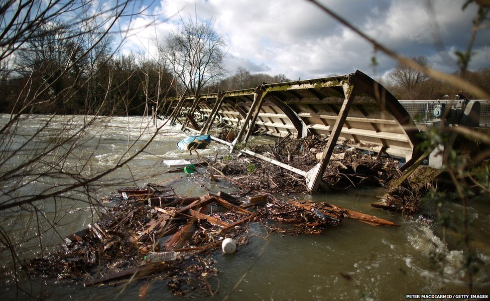A weir at Penton Hook Lock, Surrey, is surrounded by debris as the level of water in the River Thames remains high.