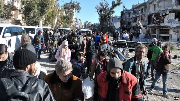People gather near UN vehicles in a besieged area of the Syrian city of Homs (12 February 2014)
