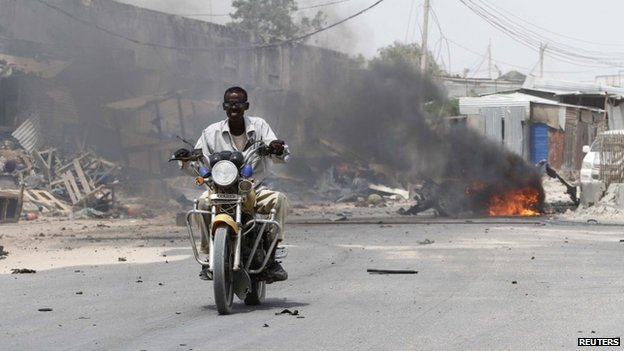 A motorcyclist rides away from the scene of an explosion near the entrance of the airport in Somalia's capital Mogadishu - 13 February 2014