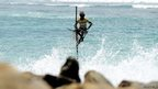 A Sri Lankan stilt fishermen works on his pole in the southern town of Galle