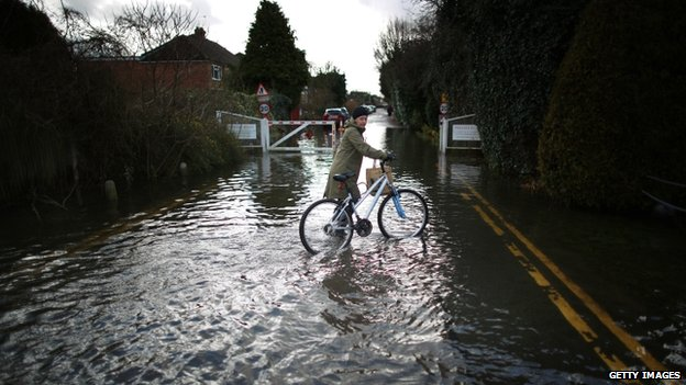 A resident pushes her bike through flood water in Staines-Upon-Thames