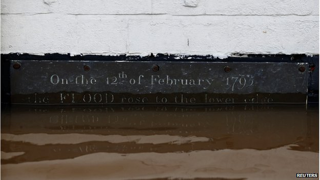 "A plaque on a wall above flood water reads ""On the 12th of February 1795 the FLOOD rose to the lower edge"" in Worester, central England"