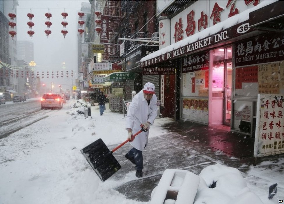 A man clears snow in front of the DC Meat Market in the Chinatown neighbourhood of New York on 13 February 2014