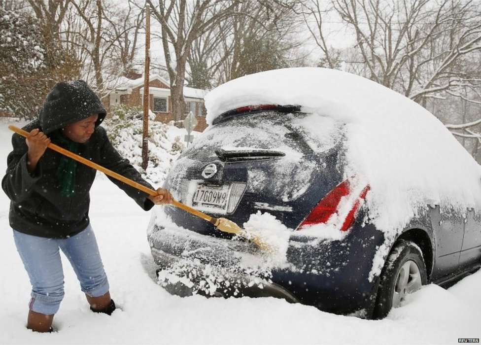 Oretha Bailey clears her car of snow in Silver Spring, Maryland, on 13 February 2014