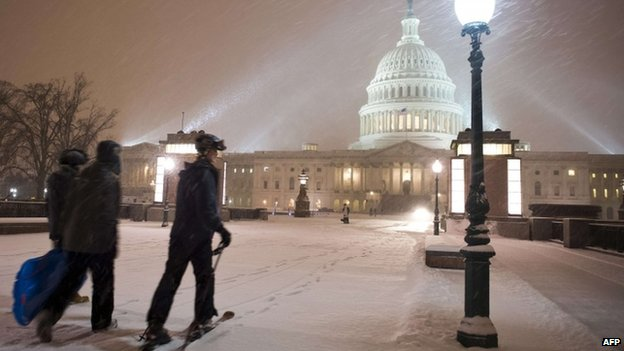 A young man on skis and his friends pass in front of the US Congress building as a heavy snow storm hits Washington DC on 13 February 2014