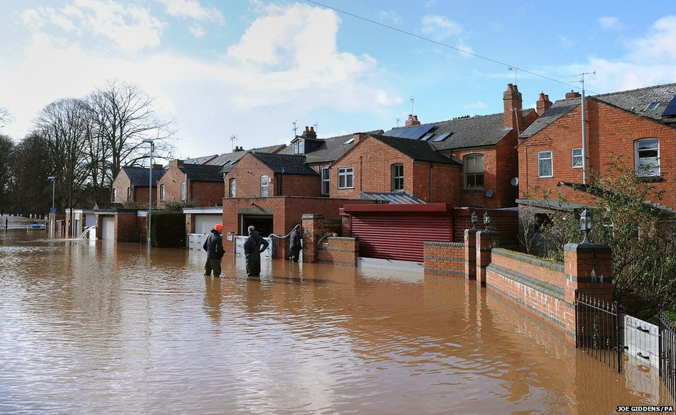 Residents of Waterworks Road in Worcester wade through the floodwater outside their home