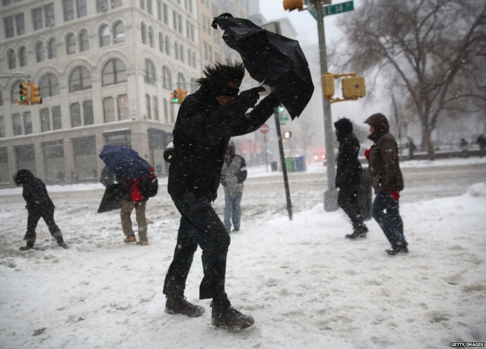 A man walks through the snow in New York City on 13 February 2014