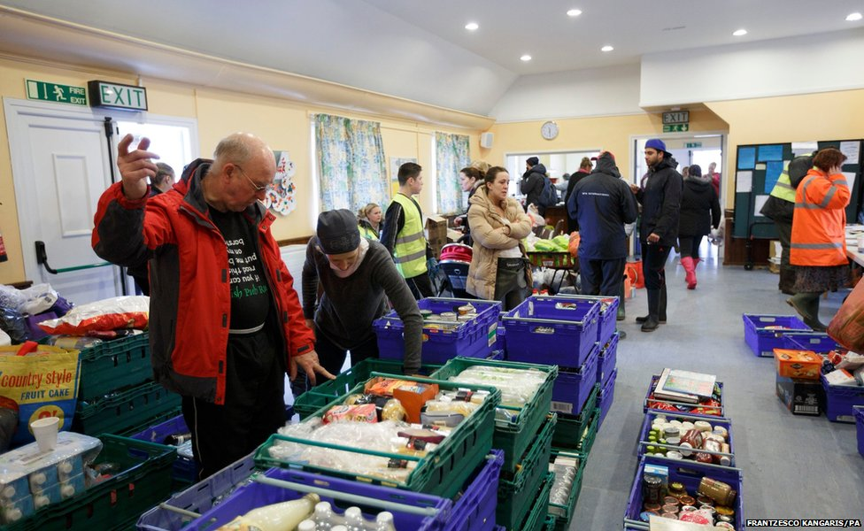 At St Paul's Church in Egham, Surrey, volunteers sort food parcels donated for people affected by severe flooding in the area.