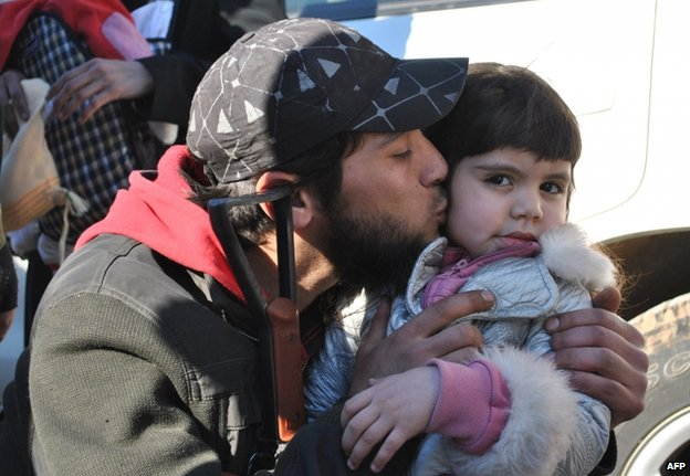 A rebel fighter kisses a little girl goodbye in Homs, 12 February