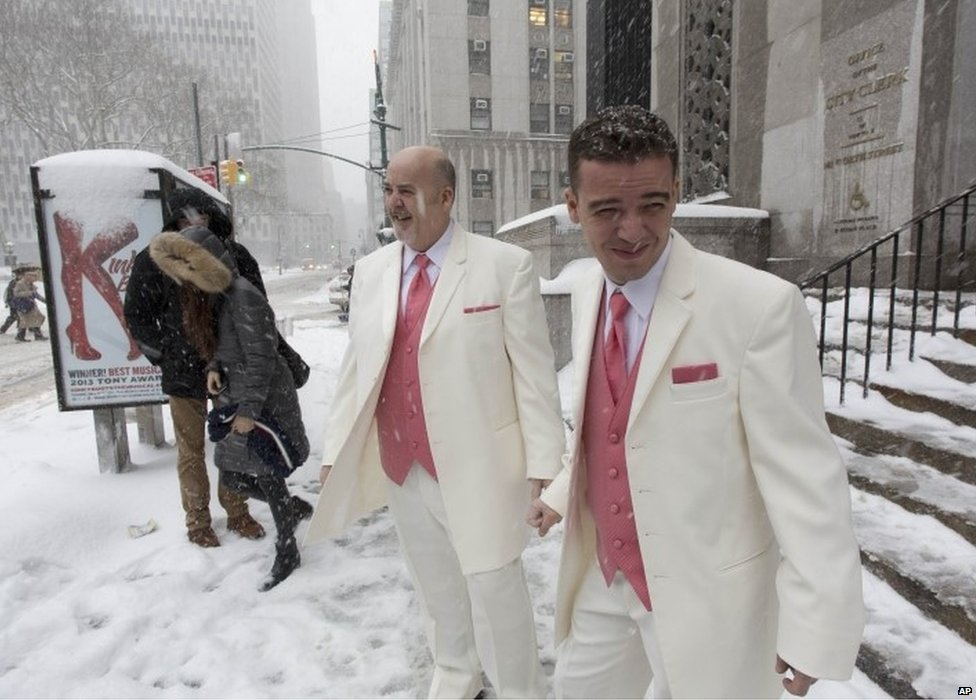 Newlyweds Steve Cosh (centre) and Thiago Cardoso look at the snow falling in Manhattan as they walk out from New York's municipal marriage bureau on 13 February 2014