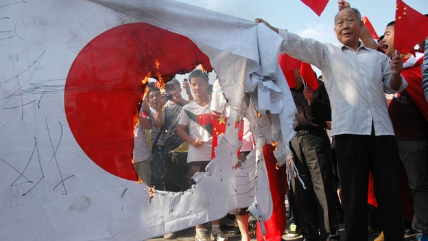 An anti Japanese protester burn a flag