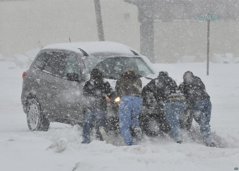 Good Samaritans help push a stranded motorist stuck in deep snow in Bethlehem, Pennsylvania, on 13 February 2014