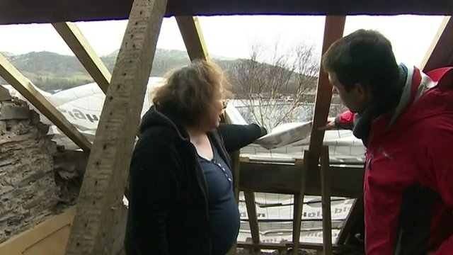 Lizzie Mowatt shows BBC reporter Hywel Griffith the damage to her house
