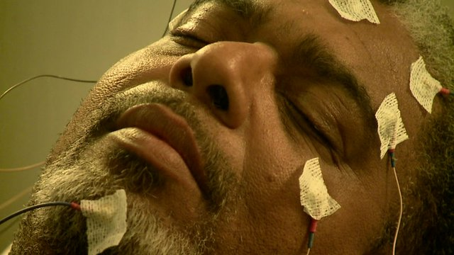 Man's face with sensors that measure sleep
