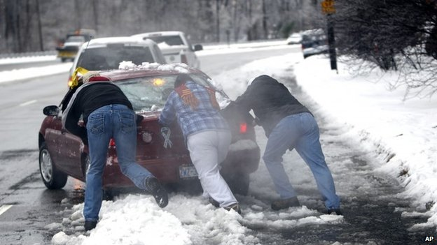People help push a car from the curb, in Raleigh, North Carolina 13 February 2014
