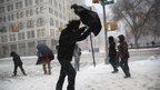 A man walks through the snow in New York City on 13 February 2014