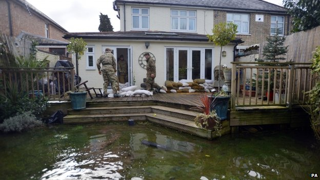 Soldiers from the Royal Welsh placing sandbags around a house in Chertsey, Surrey
