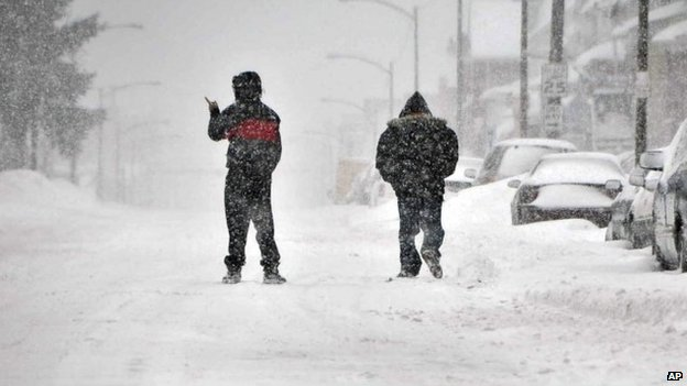 Two pedestrians brave the snow and walk along East Diamond Avenue during a winter storm in Hazelton, Pennsylvania 13 February 2014