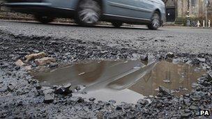 A car drives past a pothole