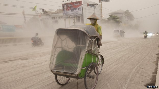 A man wears a mask as he rides a rickshaw on a road covered with ash from Mount Kelud, in Yogyakarta, 14 February 2014