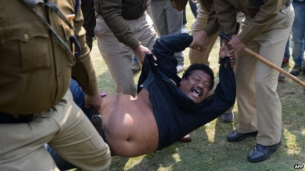 A demonstrator demanding a separate state of Telangana is detained by Indian policemen outside the parliament building in New Delhi on February 13, 2014.