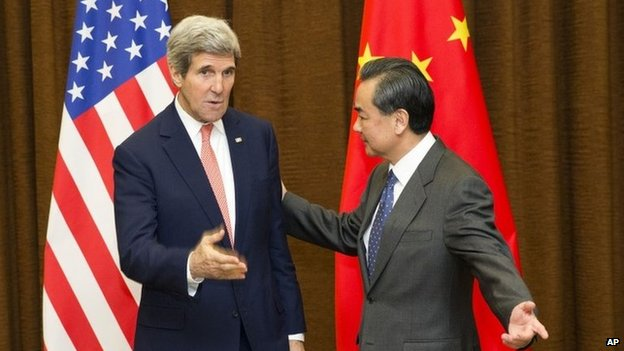 US Secretary of State John Kerry, left, is greeted by Chinese Foreign Minister Wang Yi at the Ministry of Foreign Affairs in Beijing, China, Friday, 14 February 2014