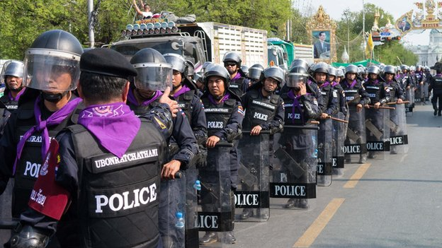 Police wait at the Rachadamnoen, Bangkok, on 14 February 2014