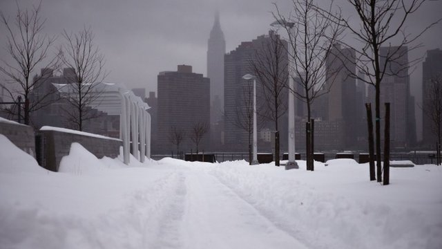 The Empire State Building and the skyline is seen from a path of snow in the Queens borough of New York