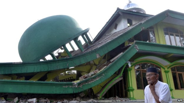 An elderly man walks past a collapsed mosque in Kranggan village after an earthquake in Banyumas, Central Java, on 25 January 2014