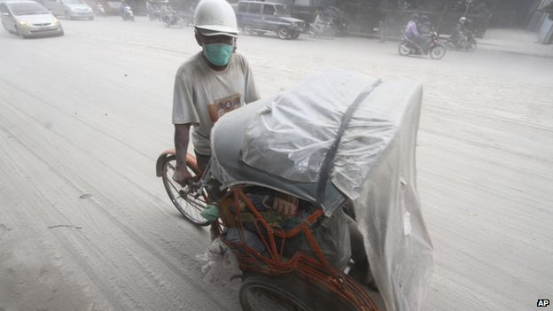 A pedicab makes its way on a street covered with volcanic ash from an eruption of Mount Kelud, in Solo, Indonesia, 14 February 2014