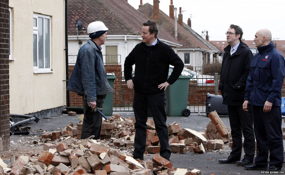 Prime Minister David Cameron talks to a builder in Blackpool, Lancashire