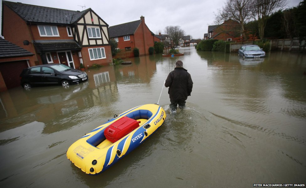 A resident pulls a boat towards his house in a flooded street near Staines-Upon-Thames