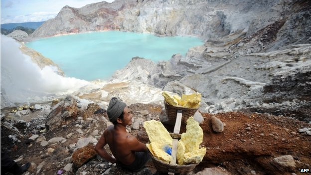 This photo taken on 1 February 2014 shows a miner carrying blocks of sulphur from Ijen crater in Banyuwangi, East Java