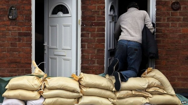 Man climbing over sand bags in Gloucester