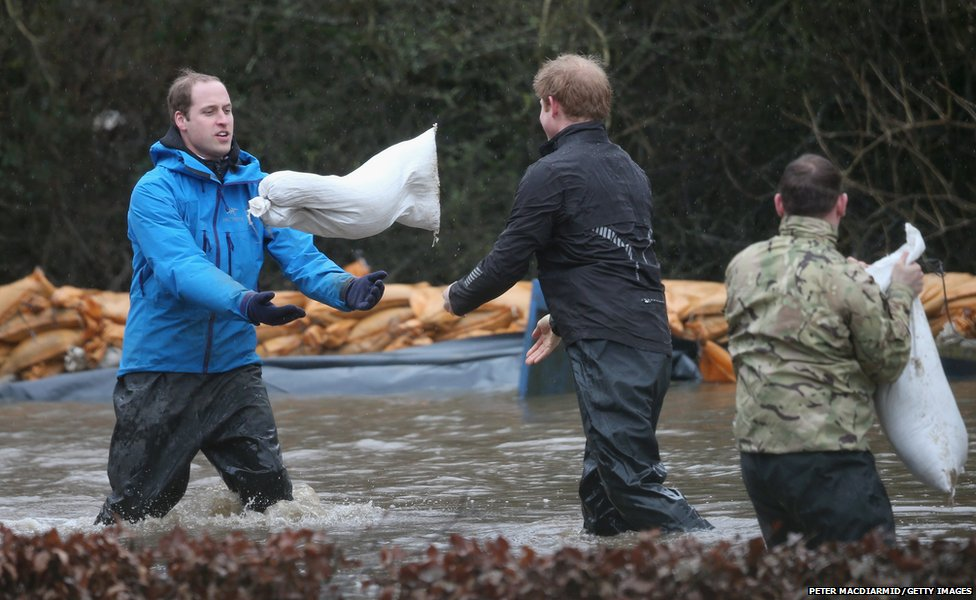 Princes William and Harry have joined troops trying to protect homes from storms sweeping southern Britain.