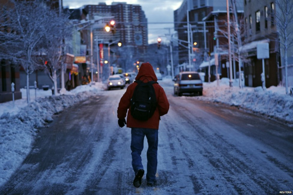 A man makes his commute after a night of snow in Jersey City, New Jersey on 14 February 2014