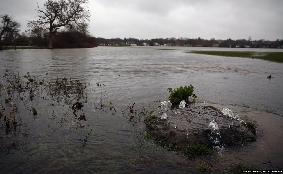 A drain gushes with water in a flooded field next to the River Thames